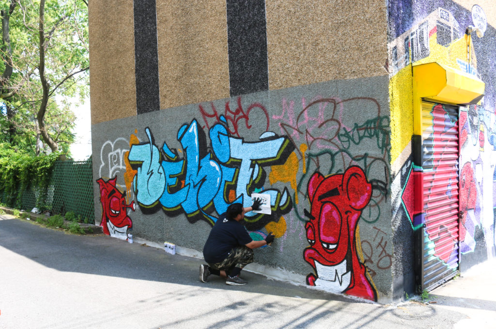 Street artist Bekit painting mural at Welling Court in Astoria, Queens