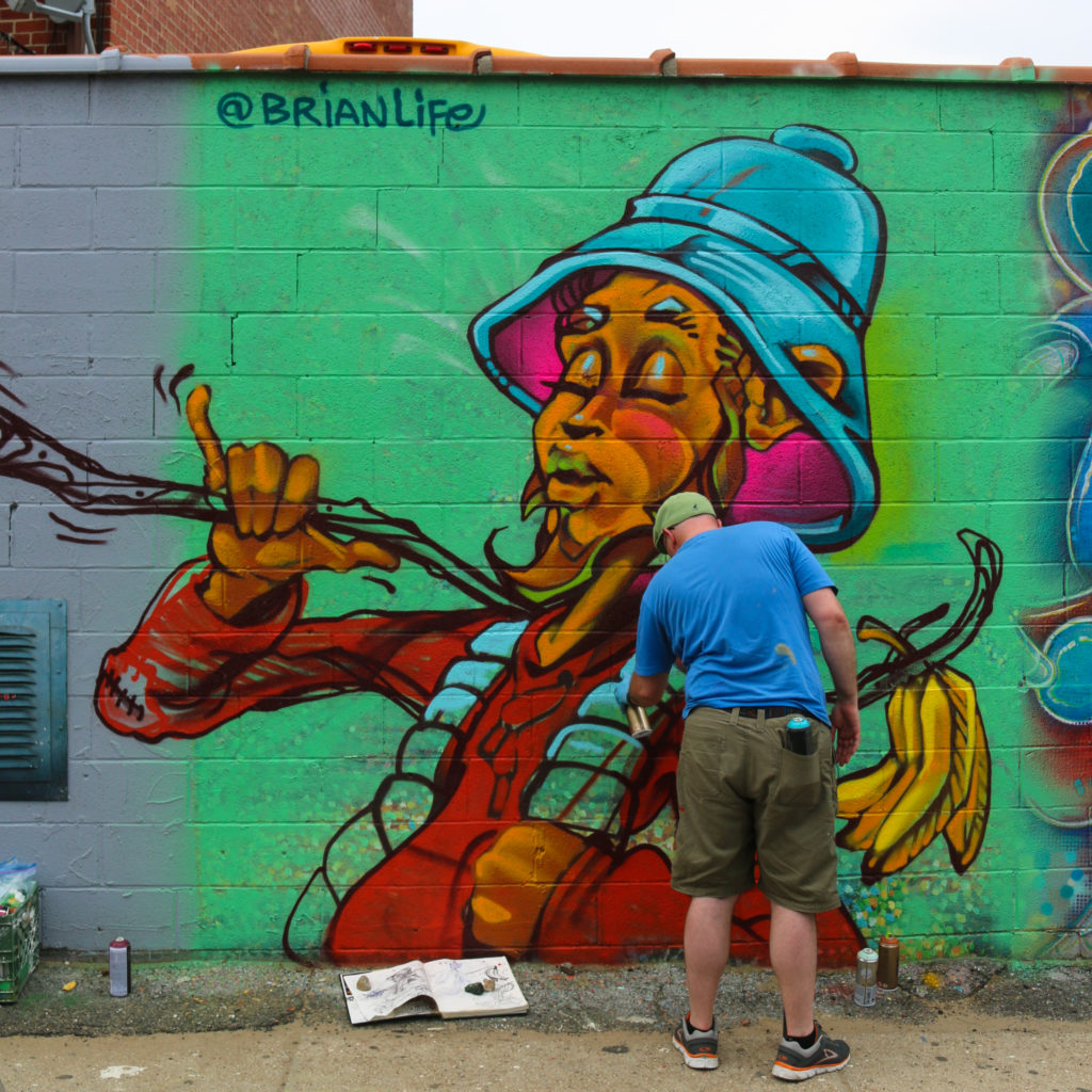 Street artist Brian Life painting mural at Welling Court in Astoria, Queens