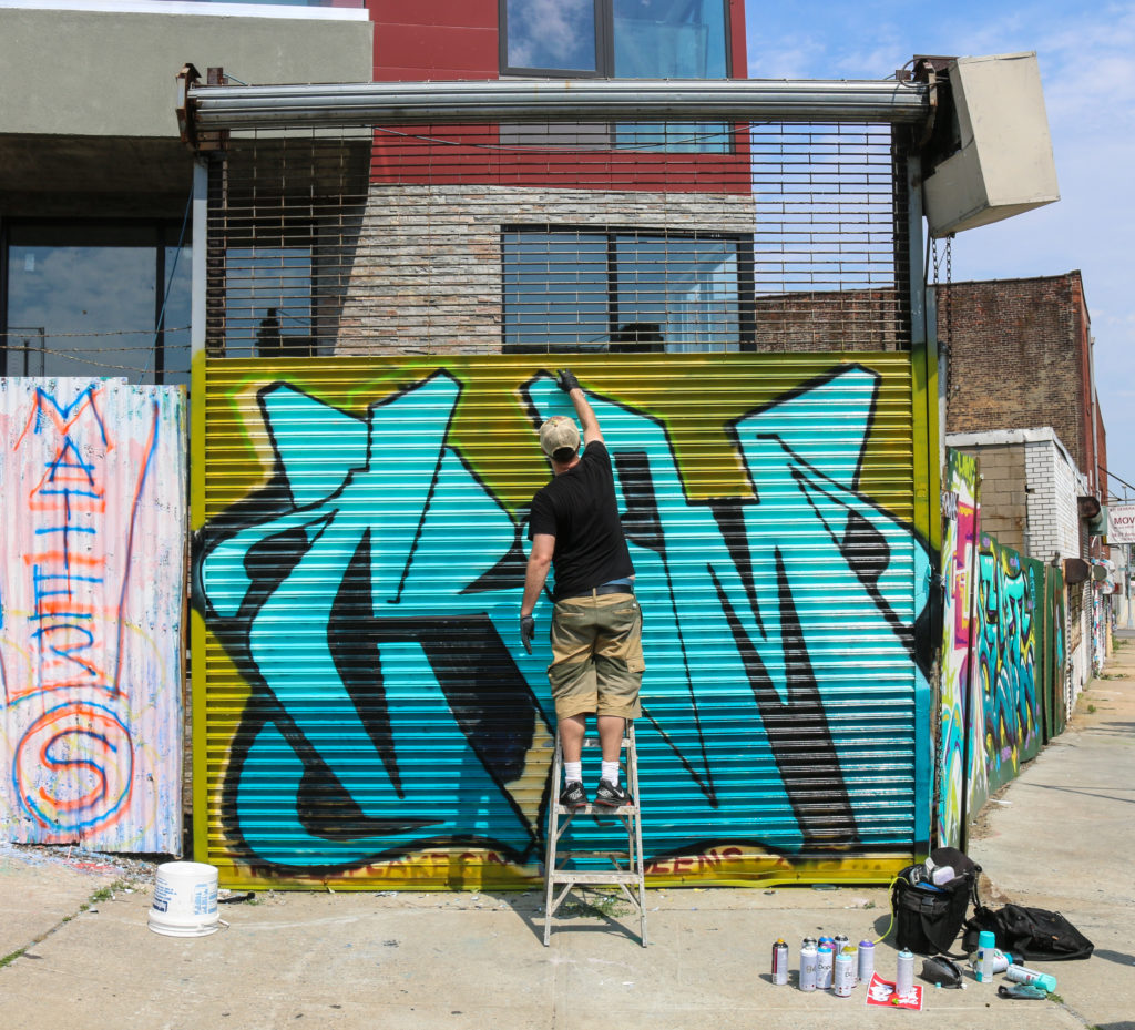 Street artist Cram painting mural at Welling Court in Astoria, Queens