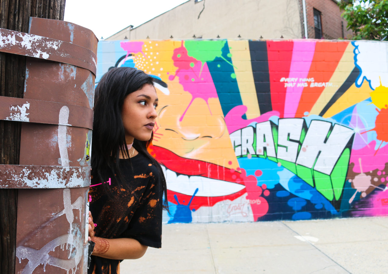 Model in front of street art mural by Crash at Welling Court in Astoria, Queens