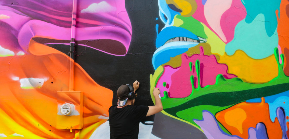 Artist Dasic Fernandez painting a street art mural at the Bushwick Collective block party in Brooklyn