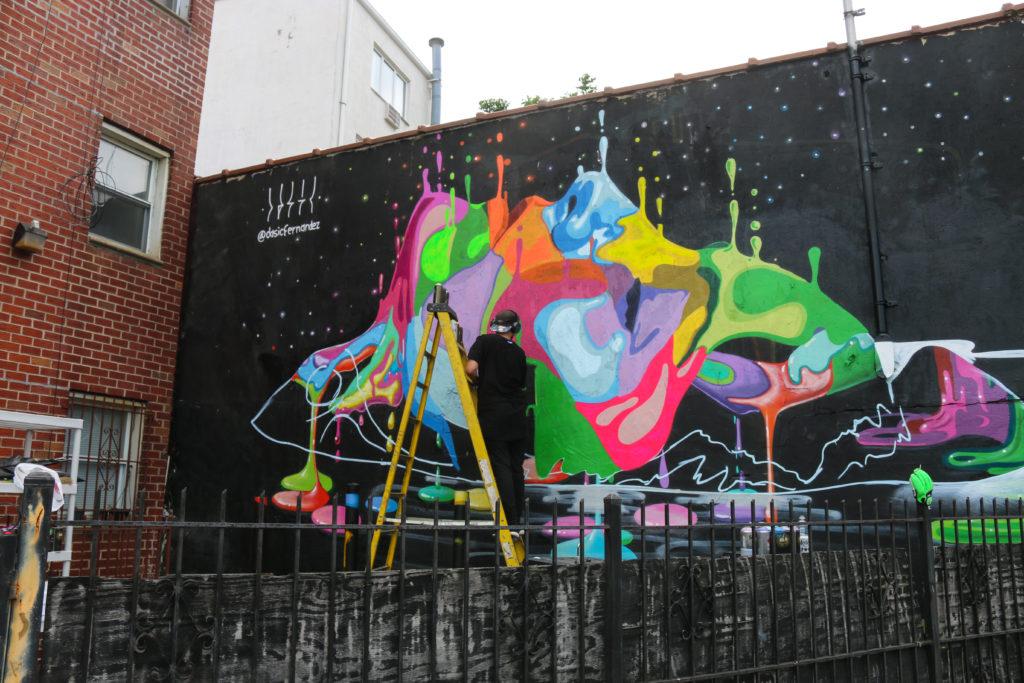 Street artist Dasic Fernandez painting mural at Welling Court in Astoria, Queens