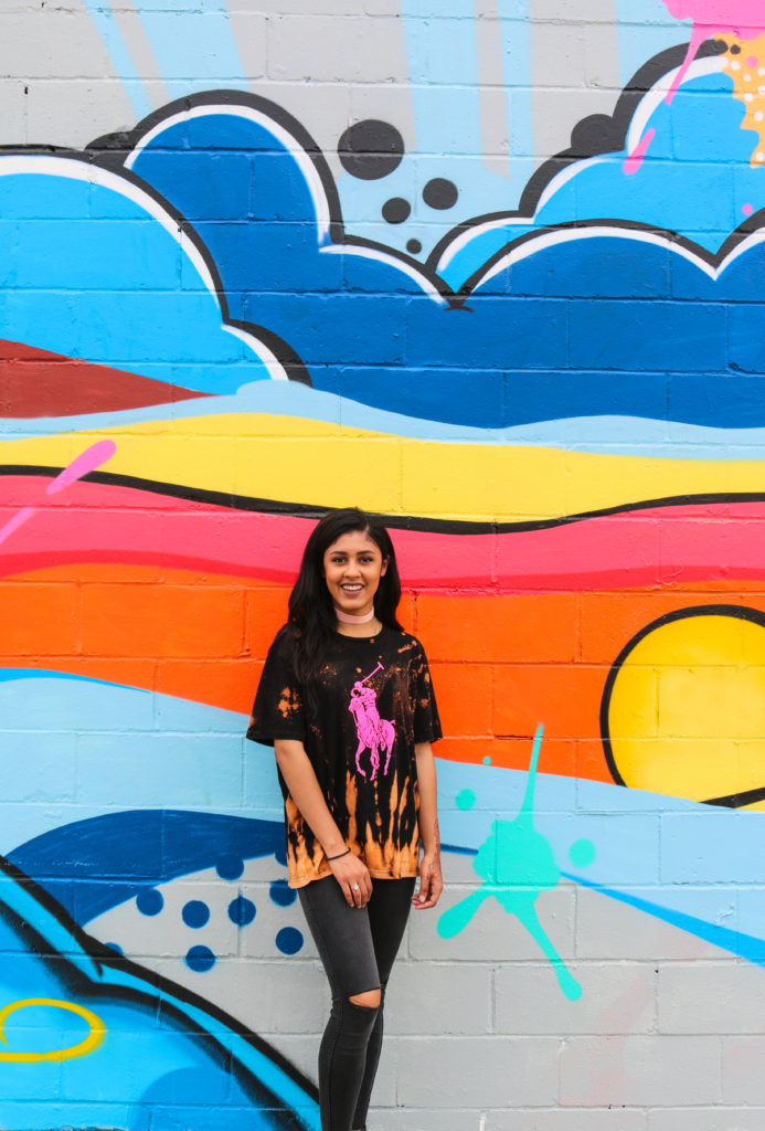 Model in front of street art mural by Daze at Welling Court in Astoria, Queens