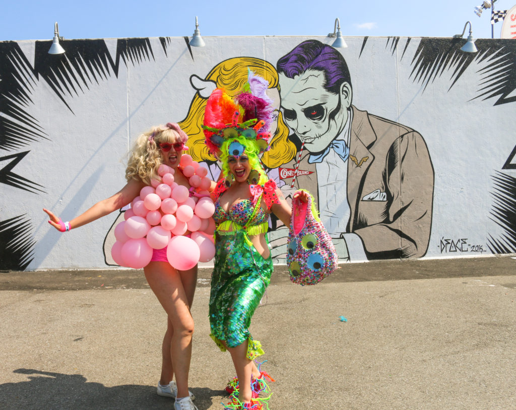 Girls posing in front of street art mural by D*Face during the mermaid parade in Coney Island