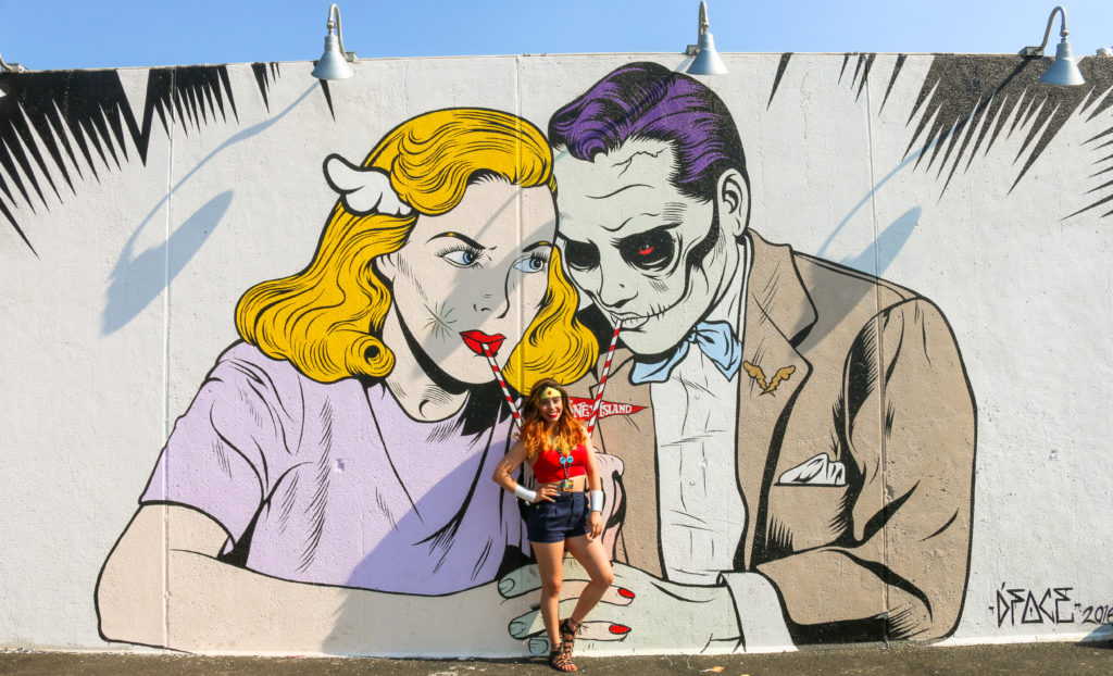 Girl posing in front of street art mural by D*Face during the mermaid parade in Coney Island