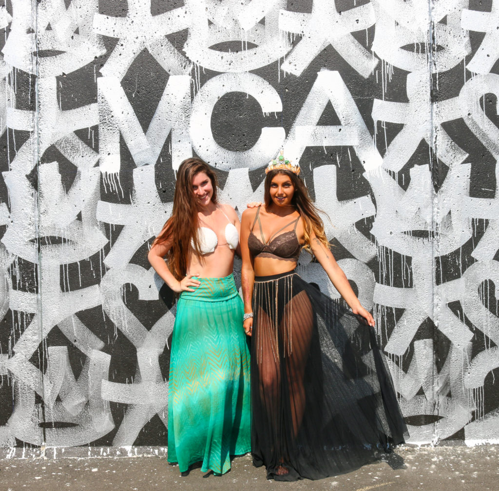 Girls posing in front of street art mural by Eric Haze during the mermaid parade in Coney Island