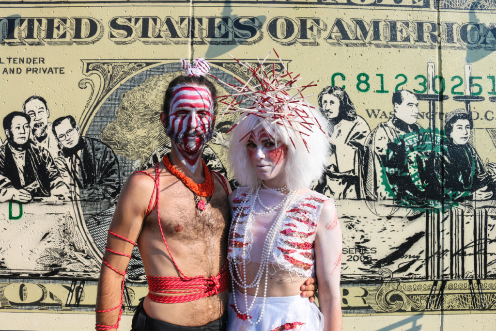 People in costume posing in front of street art mural by Icy & Sot during the mermaid parade in Coney Island