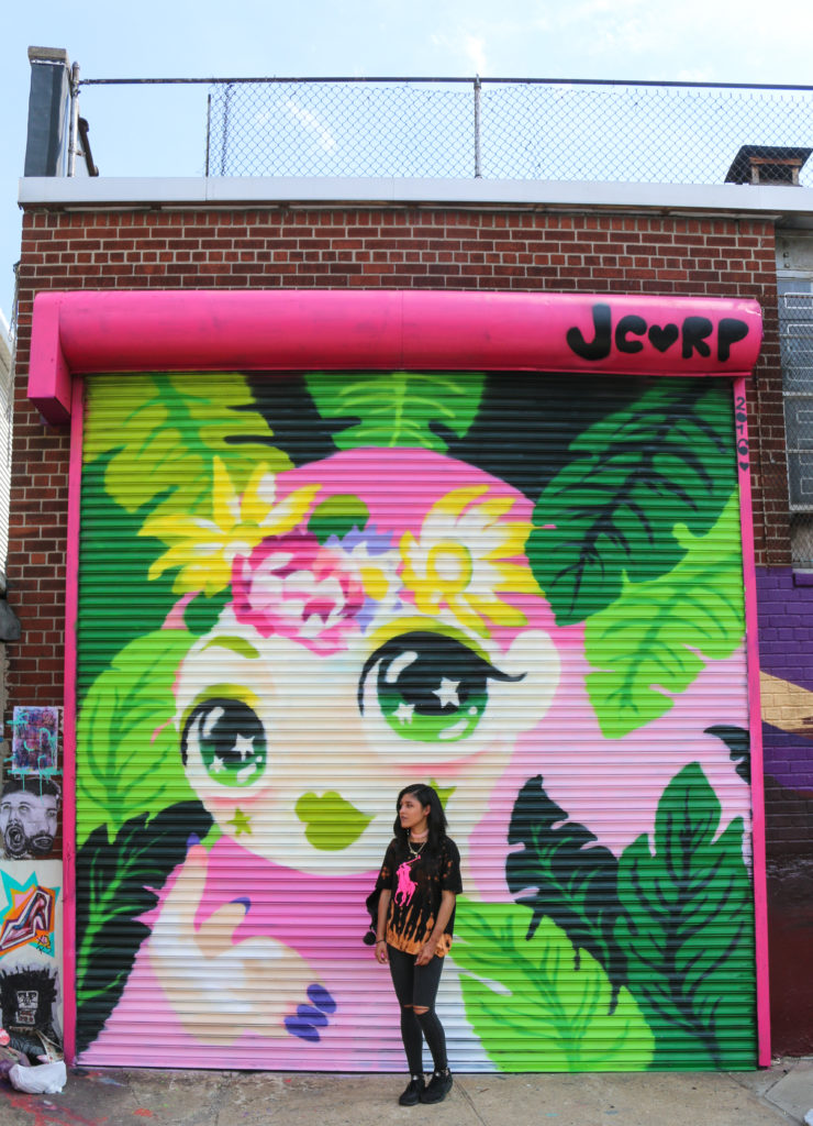 Model in front of street art mural by Jcorp at Welling Court in Astoria, Queens