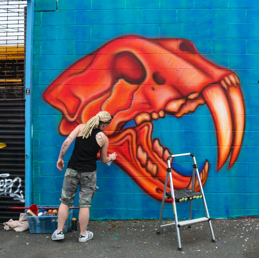 Street artist Jenna Morello painting mural at Welling Court in Astoria, Queens