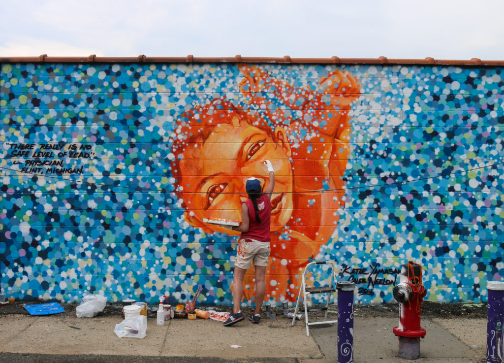 Street art mural reflecting the Flint water crisis by Katie Yamasaki and Caleb Neelon at Welling Court in Astoria, Queens