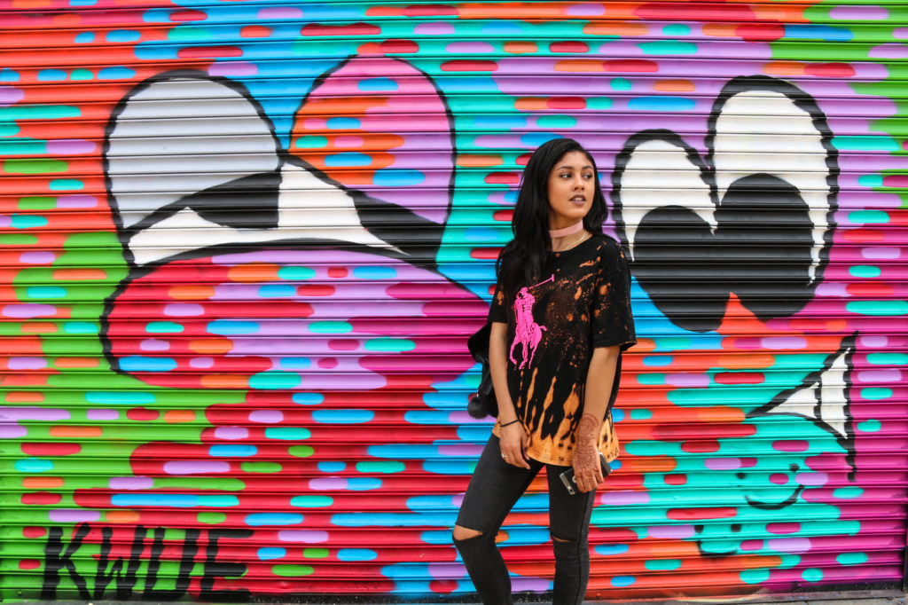 Model in front of street art mural by Kwue Molly at Welling Court in Astoria, Queens