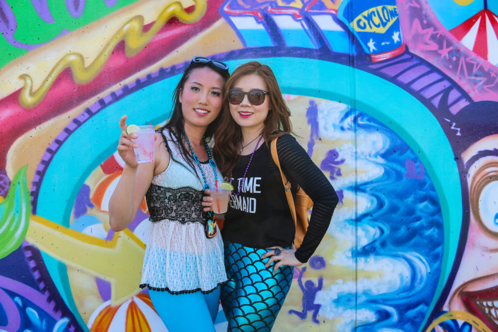 Girls posing in front of street art mural by Lady Pink during the mermaid parade in Coney Island