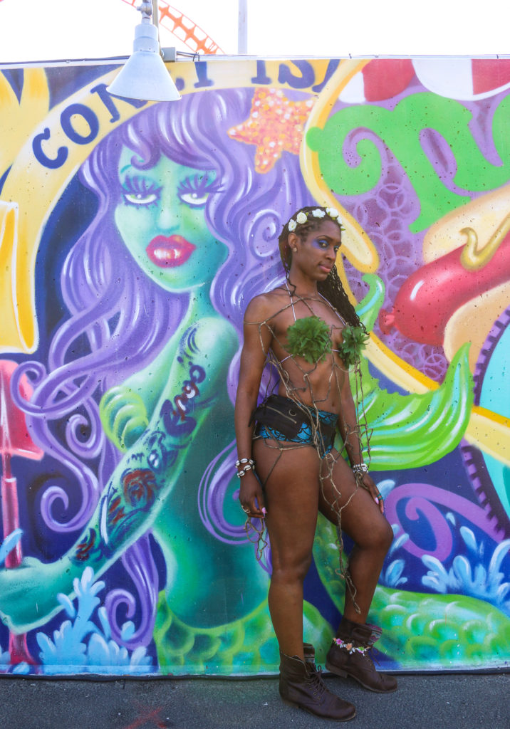 Girl posing in front of street art mural by Lady Pink during the mermaid parade in Coney Island