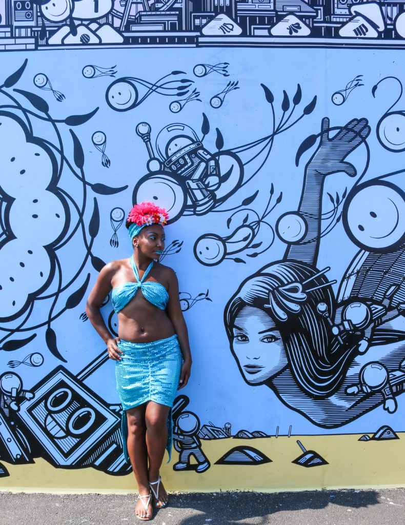 Girl posing in front of street art mural by London Police during the mermaid parade in Coney Island