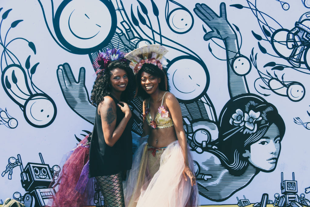 Girls posing in front of street art mural by London Police during the mermaid parade in Coney Island