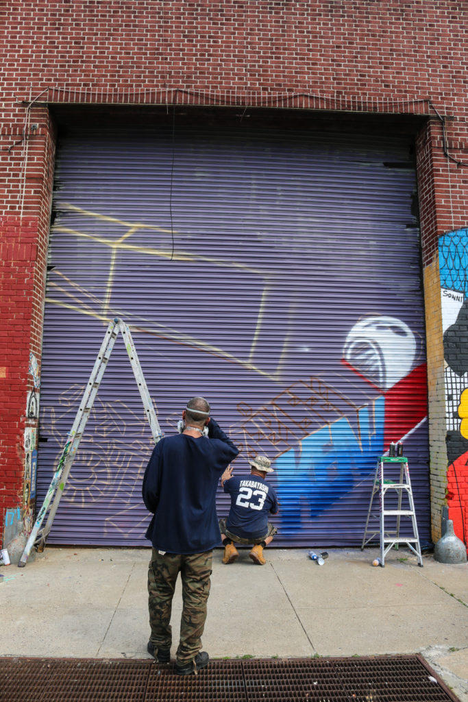 Street artists Meres One and Kenji painting mural at Welling Court in Astoria, Queens