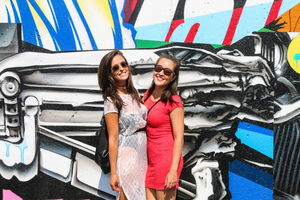 Girls posing in front of street art mural by Pose during the mermaid parade in Coney Island