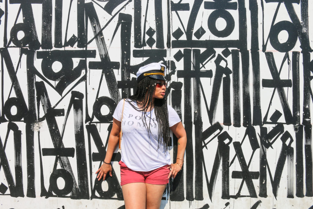 Girl posing in front of street art mural by Retna during the mermaid parade in Coney Island