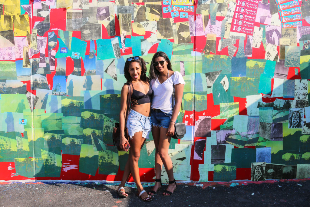 Girls posing in front of street art mural by Sam Vernon during the mermaid parade in Coney Island