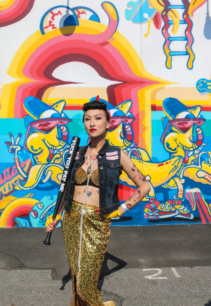 Girl posing in front of street art mural by Sheryo & The Yok during the mermaid parade in Coney Island