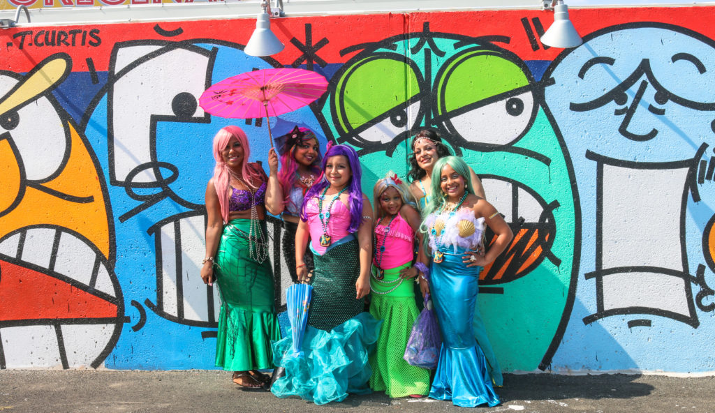 Girls posing in front of street art mural by Timothy Curtis during the mermaid parade in Coney Island