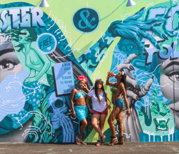 Girls posing in front of street art mural by Tristan Eaton during the mermaid parade in Coney Island