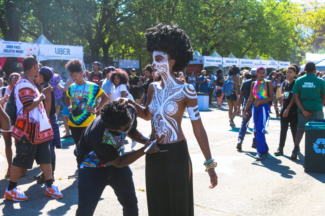 Artist body painting model at the Afropunk festival in Brooklyn