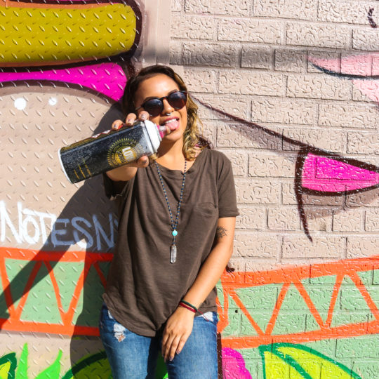 Artist Love Notes posing with her street art mural at the Bushwick Collective block party in Brooklyn