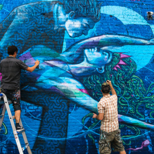 Street artists Chris Soria and Marc Evan painting mural at Welling Court in Astoria, Queens
